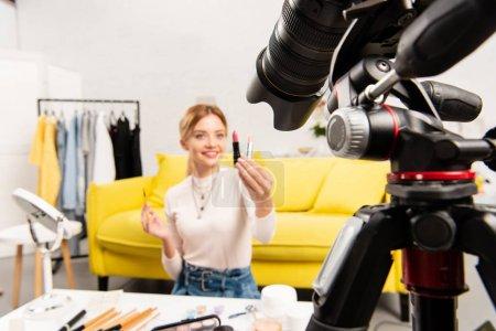 Photo pour Selective focus of beauty blogger holding lipsticks in front of video camera - image libre de droit