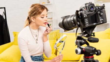 Photo for Beauty blogger holding mirror and applying lipstick in front of video camera - Royalty Free Image