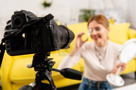 selective focus of beauty blogger curling eyelashes in front of video camera
