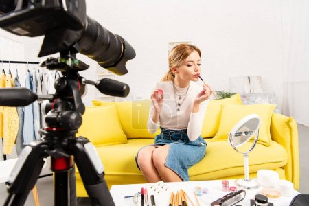 Photo for Beauty blogger applying lip gloss in front of video camera - Royalty Free Image