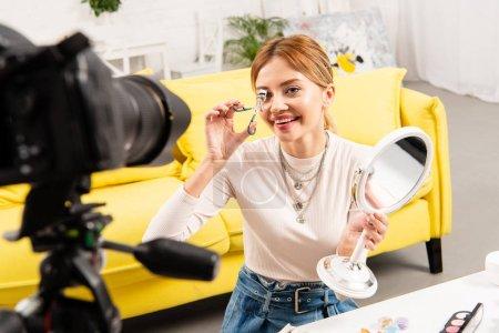 Photo pour Blogueur beauté souriant tenant miroir et cils de curling devant la caméra vidéo - image libre de droit