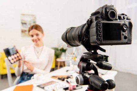 Photo pour Mise au point sélective de la beauté blogueur tenant des ombres à paupières en face de la caméra vidéo - image libre de droit