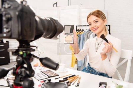Photo pour Blogueur beauté montrant visage poudre et pinceau cosmétique devant la caméra vidéo - image libre de droit