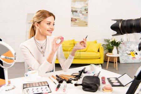 Photo pour Blogueur beauté souriant montrant brillant à lèvres et pinceau cosmétique devant la caméra vidéo - image libre de droit