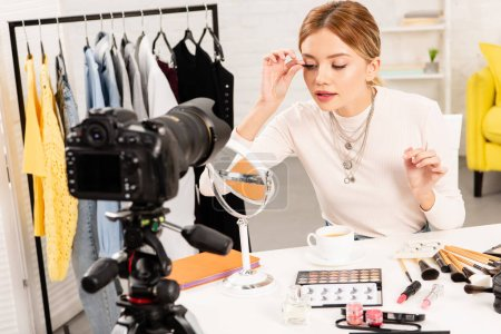 Foto de Beauty blogger applying false eyelashes in front of video camera at home - Imagen libre de derechos