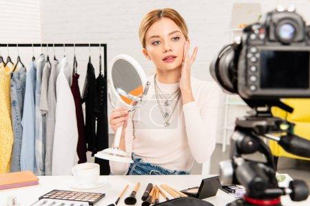 Photo pour Blogueur beauté tenant miroir et toucher le visage devant la caméra vidéo - image libre de droit