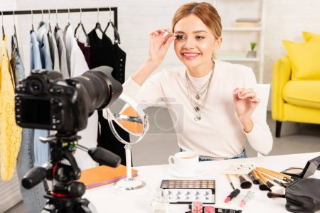 Photo for Smiling beauty blogger applying false eyelashes in front of video camera - Royalty Free Image