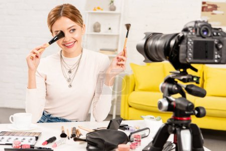 smiling beauty blogger holding cosmetic brushes in front of video camera
