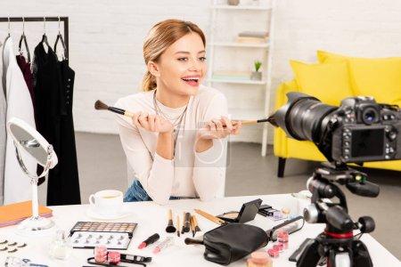 Photo pour Blogueur de beauté souriant retenant des brosses cosmétiques devant la caméra vidéo - image libre de droit