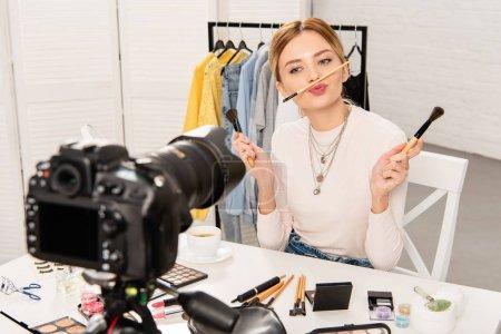 Photo pour Blogueur beauté avec des cosmétiques décoratifs tenant pinceaux cosmétiques devant la caméra vidéo - image libre de droit