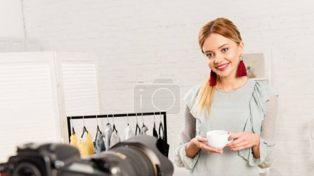 smiling blogger in earrings holding cup of coffee in front of video camera at home