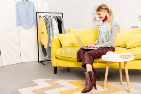 Photo pour Freelance souriant assis sur un canapé jaune et utilisant un ordinateur portable à la maison - image libre de droit
