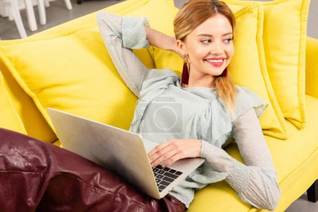 smiling freelancer lying on yellow sofa and using laptop at home