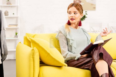 Photo pour Élégant jeune femme avec livre assis sur canapé jaune et regardant loin - image libre de droit