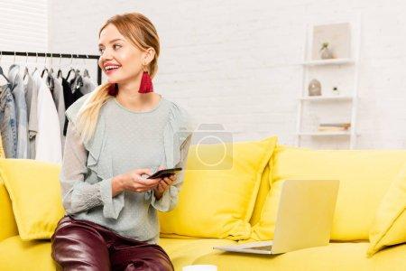 Photo pour Charmante pigiste dans des boucles d'oreilles tendance assis sur un canapé jaune et utilisant un smartphone à la maison - image libre de droit