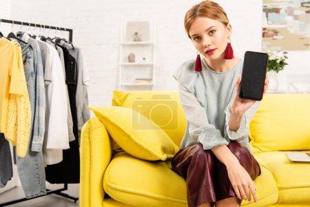 Photo pour Charmante fille dans des boucles d'oreilles à la mode assis sur un canapé jaune et en utilisant smartphone à la maison - image libre de droit
