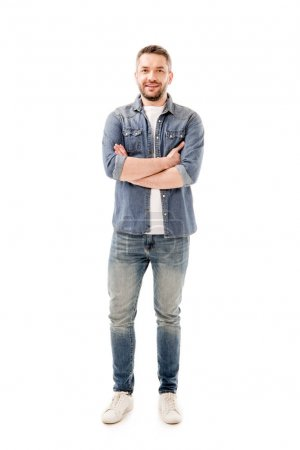 full length view of smiling bearded man in jeans standing with crossed arms isolated on white