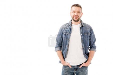 Photo pour Vue de face de l'homme barbu souriant en chemise denim debout avec les mains dans des poches isolées sur blanc - image libre de droit