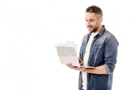 Photo pour Homme souriant en chemise denim à l'aide d'un ordinateur portable isolé sur blanc - image libre de droit