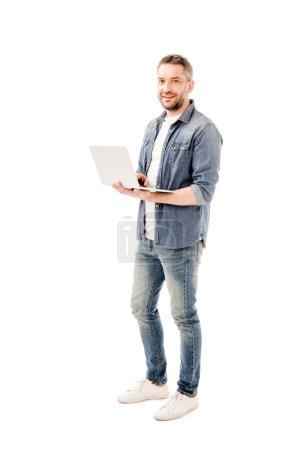 Photo pour Vue pleine longueur de l'homme souriant en chemise en denim tenant ordinateur portable isolé sur blanc - image libre de droit