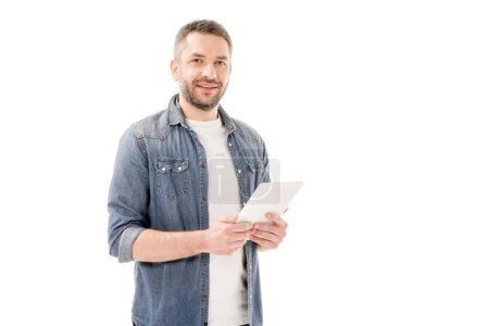 Lächelnder bärtiger Mann im Jeanshemd mit digitalem Tablet und Blick auf Kamera isoliert auf weiß