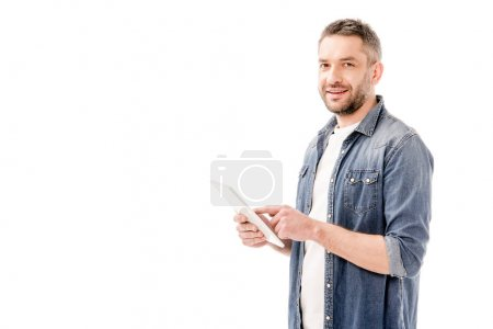 hombre barbudo sonriente en camisa vaquera usando tableta digital y mirando a la cámara aislada en blanco