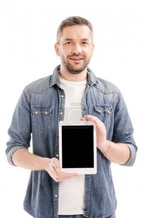 Vorderseite eines lächelnden bärtigen Mannes im Jeanshemd, der ein digitales Tablet mit leerem Bildschirm hält, isoliert auf weiß