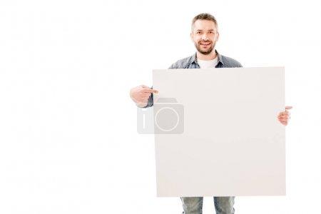 Photo pour Vue de face de l'homme barbu souriant tenant une pancarte vierge isolée sur blanc - image libre de droit