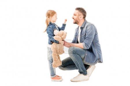 Photo pour Vue latérale de la fille avec l'ours de nounours et le papa barbu regardant l'un l'autre isolé sur le blanc - image libre de droit
