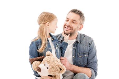 Photo pour Papa et descendant souriants avec l'ours de nounours regardant l'un l'autre d'isolement sur le blanc - image libre de droit