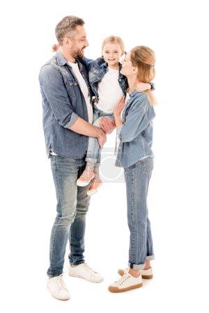 Ganzkörperansicht glücklicher Eltern in Jeans, die Tochter isoliert auf Weiß halten