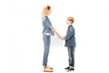 Photo for Side view of happy mother and son holding hands and looking at each other isolated on white - Royalty Free Image