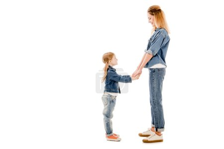 Photo for Side view of smiling mother and daughter holding hands and looking at each other isolated on white - Royalty Free Image