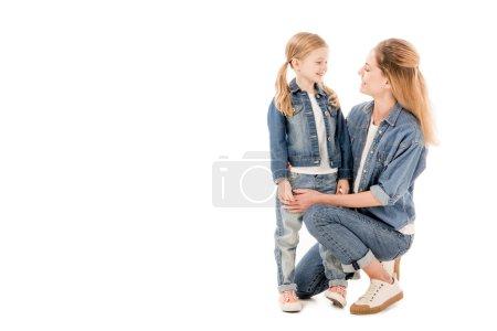 Szczęśliwa matka i córka uśmiechając się patrząc na siebie na białym tle