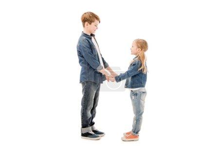 Photo pour Vue latérale des gosses se tenant des mains et regardant l'un l'autre isolé sur le blanc - image libre de droit