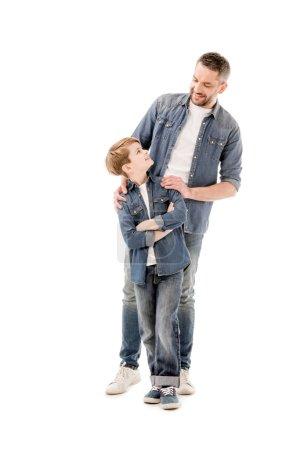 Photo pour Vue pleine longueur du père et du fils souriants se regardant isolés sur blanc - image libre de droit