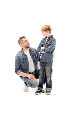 Photo pour Père et fils souriants regardant l'un l'autre d'isolement sur le blanc - image libre de droit