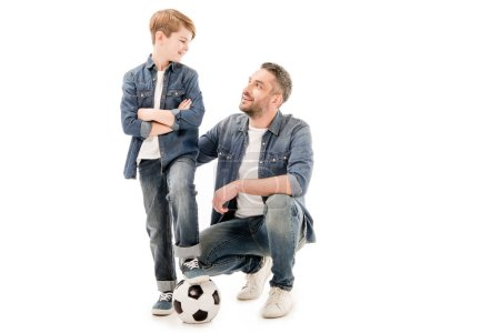 son and dad with soccer ball looking at each other isolated on white