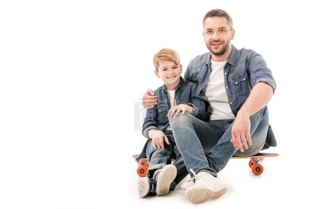 son and dad sitting on skateboard and embracing on white