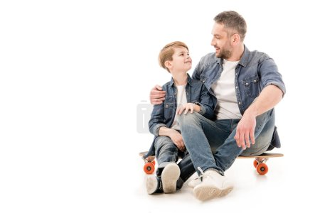 Foto de Hijo y papá sentados en el monopatín y abrazando en blanco - Imagen libre de derechos