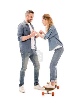 Photo pour Vue pleine longueur du couple avec planche à roulettes tenant les mains isolées sur blanc - image libre de droit
