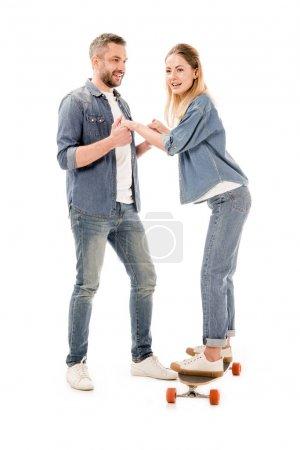 vue pleine longueur du couple avec planche à roulettes tenant les mains isolées sur blanc
