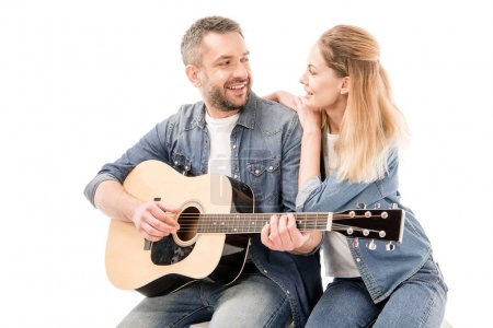 Photo for Smiling man in jeans playing acoustic guitar for wife isolated on white - Royalty Free Image