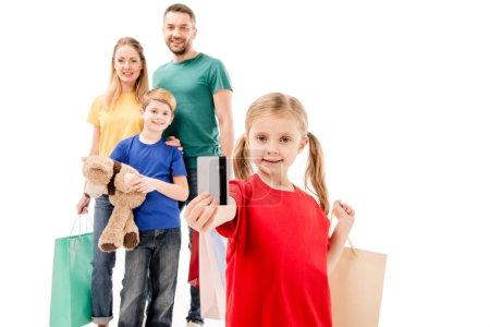 Photo pour Famille de sourire avec des sacs à provisions d'isolement sur le blanc - image libre de droit