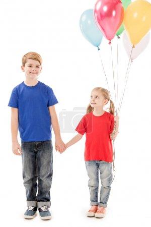 Photo pour Vue pleine longueur de deux gosses avec des ballons colorés retenant des mains d'isolement sur le blanc - image libre de droit