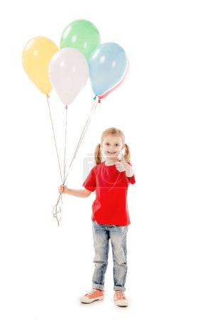 Photo pour Vue pleine longueur du gamin souriant tenant des ballons colorés et montrant pouce vers le haut isolé sur blanc - image libre de droit