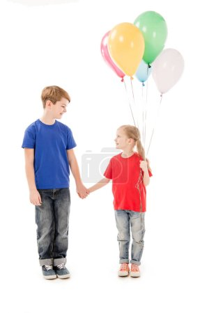 Photo for Full length view of two kids with colorful balloons holding hands isolated on white - Royalty Free Image