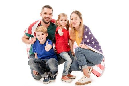 Photo pour Famille souriante avec drapeau américain regardant la caméra et montrant pouces isolés sur blanc - image libre de droit