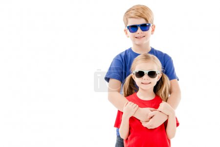 Photo pour Vue de face de soeur et frère dans des lunettes de soleil embrassant isolé sur blanc - image libre de droit