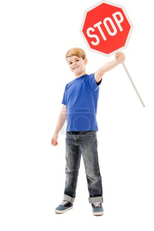 full length view of smiling boy holding stop sign isolated on white